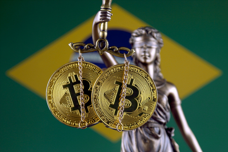 Symbol of law and justice, physical version of Bitcoin and Brazil Flag. Prohibition of cryptocurrencies, regulations, restrictions or security, protection, privacy.