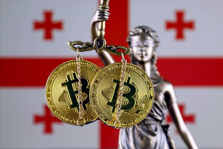 Symbol of law and justice, physical version of Bitcoin and Georgia Flag. Prohibition of cryptocurrencies, regulations, restrictions or security, protection, privacy.