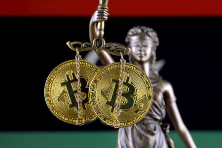 Symbol of law and justice, physical version of Bitcoin and Libya Flag. Prohibition of cryptocurrencies, regulations, restrictions or security, protection, privacy. Zdjęcie Seryjne