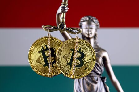 Symbol of law and justice, physical version of Bitcoin and Hungary Flag. Prohibition of cryptocurrencies, regulations, restrictions or security, protection, privacy.
