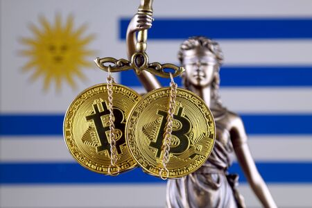 Symbol of law and justice, physical version of Bitcoin and Uruguay Flag. Prohibition of cryptocurrencies, regulations, restrictions or security, protection, privacy.