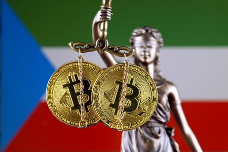 Symbol of law and justice, physical version of Bitcoin and Equatorial Guinea Flag. Prohibition of cryptocurrencies, regulations, restrictions or security, protection, privacy. Zdjęcie Seryjne