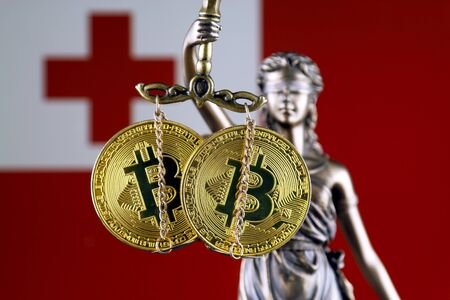Symbol of law and justice, physical version of Bitcoin and Tonga Flag. Prohibition of cryptocurrencies, regulations, restrictions or security, protection, privacy.