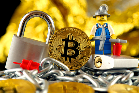 WROCLAW, POLAND - FEBRUARY 17, 2018: Physical version of Bitcoin, miner (as Lego figure), two silver padlocks and chain. Studio shot.