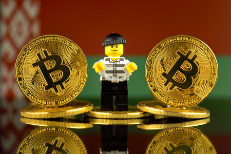 WROCLAW, POLAND - MARCH 10, 2018: Physical version of Bitcoin, Robber (as Lego figure) and Belarus Flag. Studio shot.