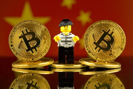 WROCLAW, POLAND - MARCH 10, 2018: Physical version of Bitcoin, Robber (as Lego figure) and China Flag. Studio shot.
