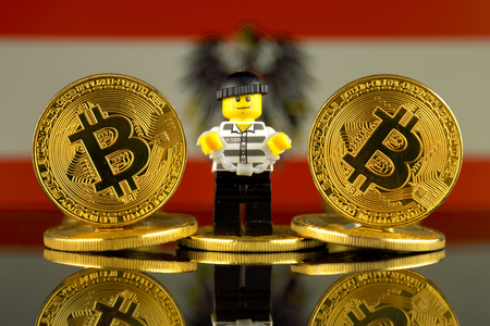 WROCLAW, POLAND - MARCH 10, 2018: Physical version of Bitcoin, Robber (as Lego figure) and Austria Flag. Studio shot. Editorial