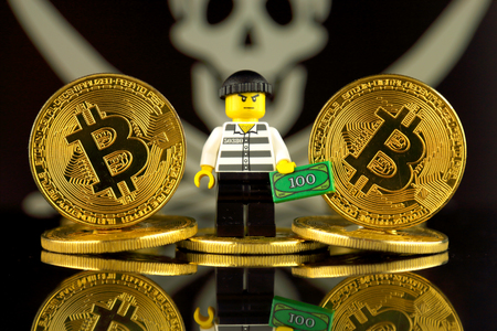 WROCLAW, POLAND - MARCH 10, 2018: Physical version of Bitcoin, Robber (as Lego figure) and Pirate Flag. Studio shot.