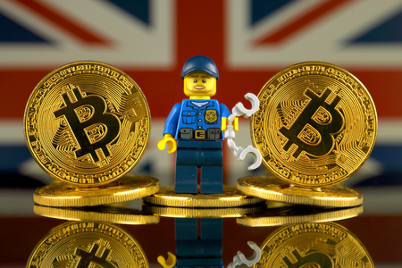 WROCLAW, POLAND - MARCH 10, 2018: Physical version of Bitcoin, Police Officer (as Lego figure) and United Kingdom Flag. Studio shot. Editorial