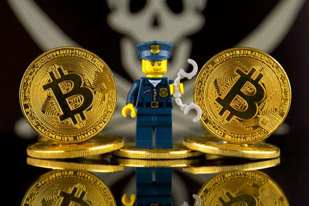 WROCLAW, POLAND - MARCH 10, 2018: Physical version of Bitcoin, Police Officer (as Lego figure) and Pirate Flag. Studio shot.