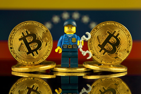 WROCLAW, POLAND - MARCH 10, 2018: Physical version of Bitcoin, Police Officer (as Lego figure) and Venezuela Flag. Studio shot.