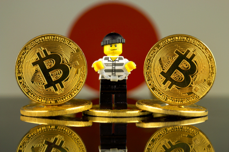 WROCLAW, POLAND - MARCH 10, 2018: Physical version of Bitcoin, Robber (as Lego figure) and Japan Flag. Studio shot. Publikacyjne