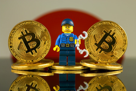 WROCLAW, POLAND - MARCH 10, 2018: Physical version of Bitcoin, Police Officer (as Lego figure) and Japan Flag. Studio shot. Publikacyjne