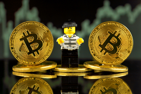 WROCLAW, POLAND - MARCH 10, 2018: Physical version of Bitcoin and Robber (as Lego figure). Studio shot. Editorial