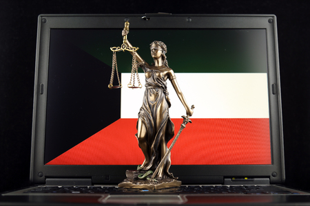 Symbol of law and justice with Kuwait Flag on laptop. Studio shot.