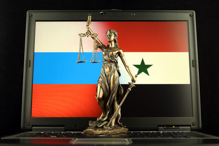 Symbol of law and justice with Russia and Syria Flag on laptop. Studio shot.
