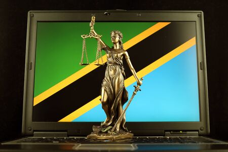 Symbol of law and justice with Tanzania Flag on laptop. Studio shot.