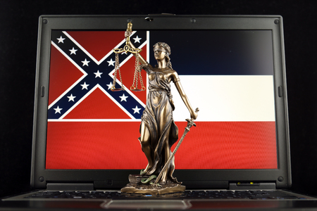 Symbol of law and justice with Mississippi State Flag on laptop. Studio shot.