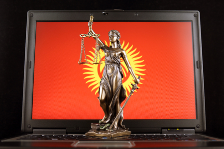 Symbol of law and justice with Kyrgyzstan Flag on laptop. Studio shot. Stock fotó