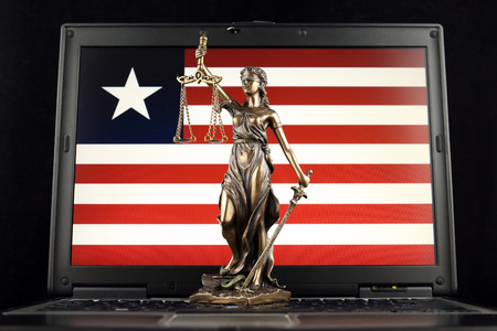 Symbol of law and justice with Liberia Flag on laptop. Studio shot.