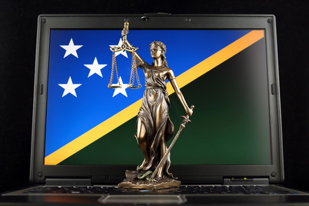 Symbol of law and justice with Solomon Islands Flag on laptop. Studio shot. Stock Photo