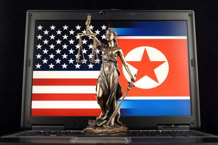 Symbol of law and justice with United States and North Korea Flag on laptop. Studio shot.