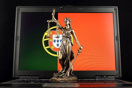 Symbol of law and justice with Portugal Flag on laptop. Studio shot.