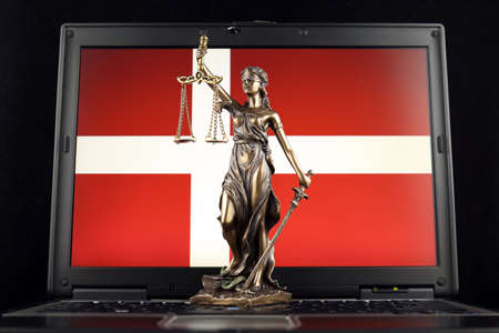 Symbol of law and justice with Denmark Flag on laptop. Studio shot.