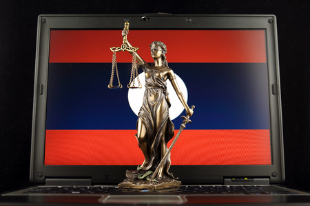 Symbol of law and justice with Laos Flag on laptop. Studio shot.