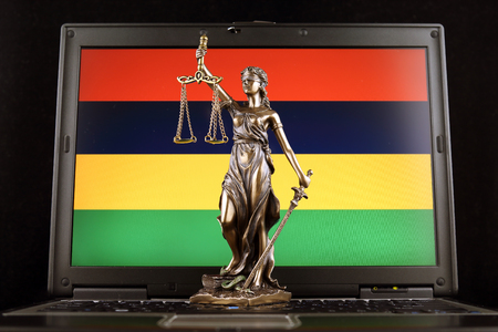 Symbol of law and justice with Mauritius Flag on laptop. Studio shot. Stock Photo