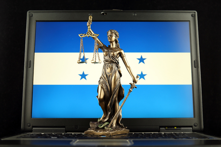 Symbol of law and justice with Honduras Flag on laptop. Studio shot.