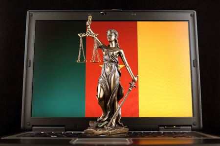 Symbol of law and justice with Cameroon Flag on laptop. Studio shot.
