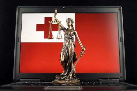 Symbol of law and justice with Tonga Flag on laptop. Studio shot.