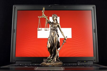 Symbol of law and justice with Switzerland Flag on laptop. Studio shot. Stock fotó
