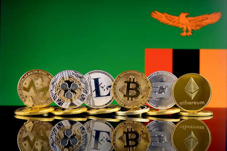 Physical version of Cryptocurrencies (Monero, Ripple, Litecoin, Bitcoin, Dash, Ethereum) and Zambia Flag. Stock Photo