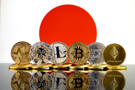Physical version of Cryptocurrencies (Monero, Ripple, Litecoin, Bitcoin, Dash, Ethereum) and Japan Flag.