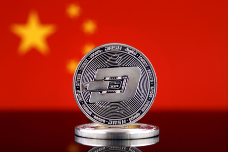 Physical version of Dash (DASH), new virtual money and China Flag. Conceptual image for worldwide cryptocurrency and digital payment system. Studio shot. Фото со стока