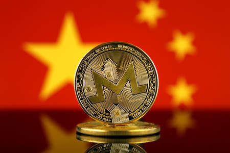 Physical version of Monero (XMR), new virtual money and China Flag. Conceptual image for worldwide cryptocurrency and digital payment system. Studio shot.