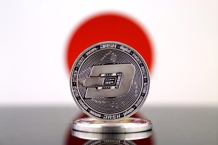 Physical version of Dash (DASH), new virtual money and Japan Flag. Conceptual image for worldwide cryptocurrency and digital payment system. Studio shot.