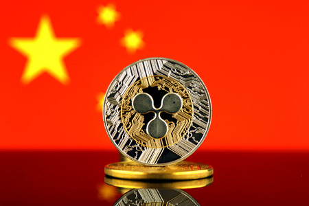 Physical version of Ripple (XRP), new virtual money and China Flag. Conceptual image for worldwide cryptocurrency and digital payment system. Studio shot.