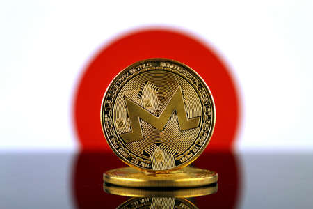 Physical version of Monero (XMR), new virtual money and Japan Flag. Conceptual image for worldwide cryptocurrency and digital payment system. Studio shot.