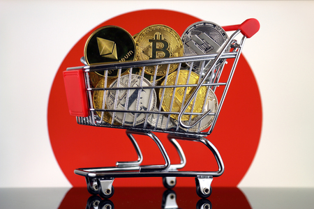 Shopping Trolley full of physical version of Cryptocurrencies (Bitcoin, Litecoin, Dash, Ethereum) and Japan Flag. Zdjęcie Seryjne