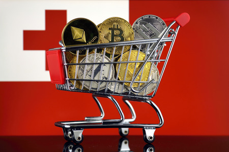 Shopping Trolley full of physical version of Cryptocurrencies (Bitcoin, Litecoin, Dash, Ethereum) and Tonga Flag. Stock Photo