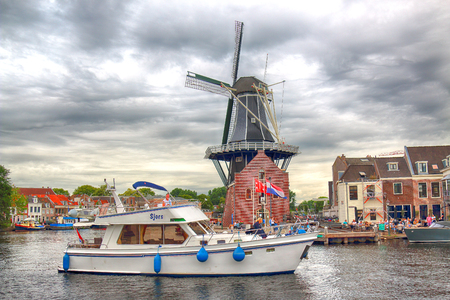 HAARLEM, NETHERLANDS - JULY 09, 2018 : Spaarne river with windmill Adriaan and beautiful clouds. Typical Dutch architecture.