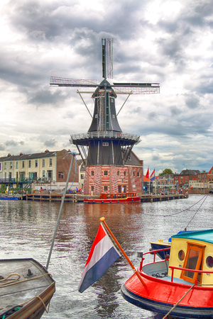 HAARLEM, NETHERLANDS - JULY 09, 2018 : Spaarne river with windmill Adriaan and beautiful clouds. Typical Dutch architecture. 版權商用圖片 - 106468345