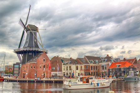 HAARLEM, NETHERLANDS - JULY 09, 2018 : Spaarne river with windmill Adriaan and beautiful clouds. Typical Dutch architecture. 版權商用圖片 - 106468413