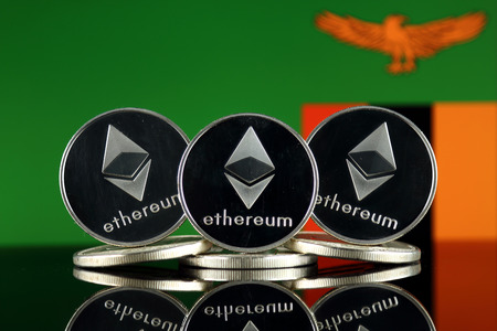 Physical version of Ethereum (ETH) and Zambia Flag. Conceptual image for investors in cryptocurrency, Blockchain Technology, Smart Contracts, Personal Tokens and Initial Coin Offering.
