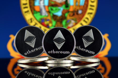 Physical version of Ethereum (ETH) and Idaho State Flag. Conceptual image for investors in cryptocurrency, Blockchain Technology, Smart Contracts, Personal Tokens and Initial Coin Offering. Фото со стока