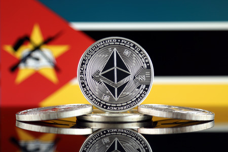 Physical version of Ethereum (ETH) and Mozambique Flag. Conceptual image for investors in cryptocurrency, Blockchain Technology, Smart Contracts, Personal Tokens and Initial Coin Offering.