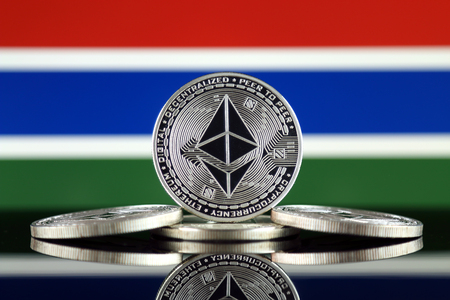 Physical version of Ethereum (ETH) and Gambia Flag. Conceptual image for investors in cryptocurrency, Blockchain Technology, Smart Contracts, Personal Tokens and Initial Coin Offering. Stock Photo